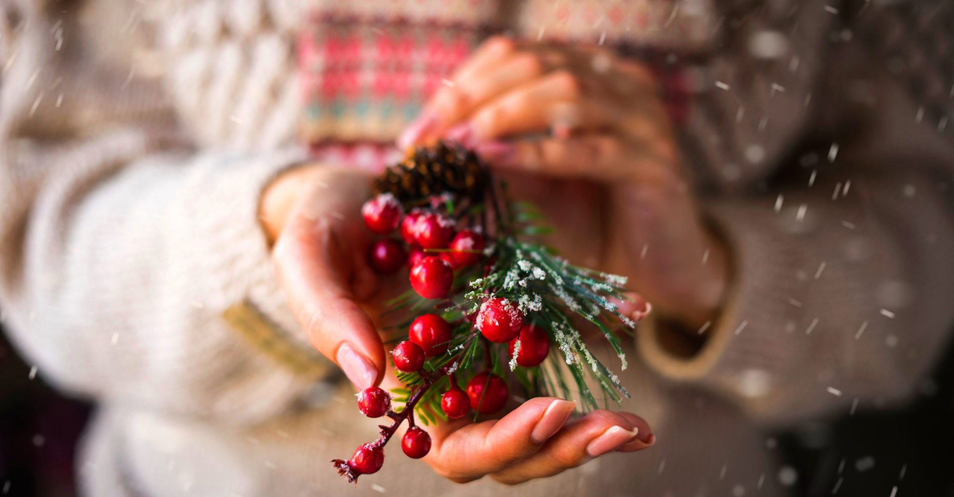 A woman in a beige knitted sweater holds in her hands a Christmas decorative ornament - a branch with red berries.; Shutterstock ID 1505358620; Purchase Order: -